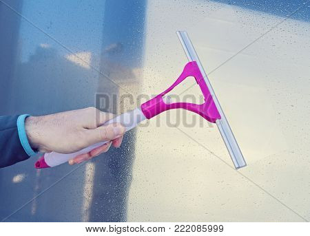 Male hand cleans glass window with Window Wiper Squeegee Season Spring cleaning concept
