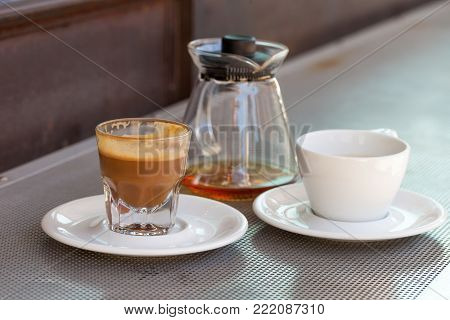 Consumed cortado coffee in a glass with ceramic white cup and teapot on metallic table and a rusty background