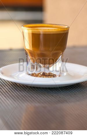 Side view of Cortado coffee in a small glass with ceramic saucer on metallic table