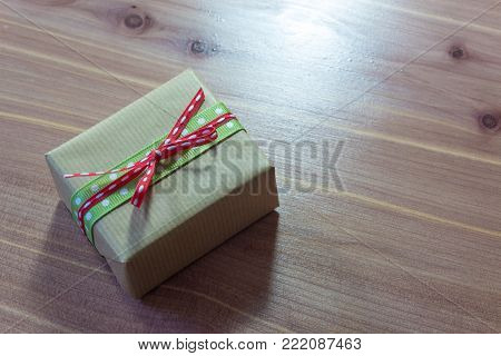 Little rustic gift box tied with green and red polka dot ribbons, on a diagonal, space for text, wood background, horizontal aspect