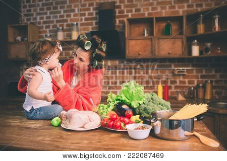 Mum at home. Young mother with little child in the home kitchen. Woman doing many tasks while looks after her baby.