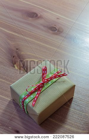 Small gift package tied with red and green polka dot ribbons on a wood background, copy space, vertical aspect