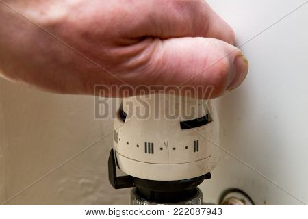 Central heating, male hand turning the dial on central heating control