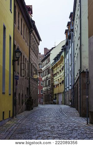 Old street in Bavarian city Nuremberg with houses different colors. Autumn mood, cloudy weather. Nurnberg, Germany
