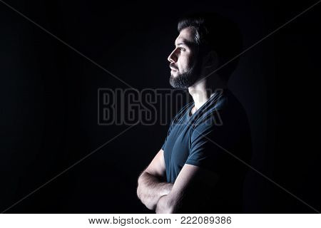 Half face. Pleasant nice handsome man standing cross handed and looking in front of him while being half face