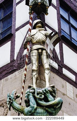 close up view of decorate of a figure of a sculpture knight with Dragon hanging on living house at the Pilatushaus in Nuremberg, Middle Franconia, Bavaria, Germany, Europe