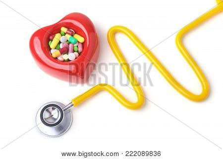 Red heart, asorted pils and a stethoscope on white background