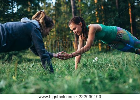 Two girls doing buddy workout outdoors performing push-ups to clap on grass.