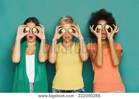 Three beautiful girls in colourful clothes having fun, covering eyes with cucumber pieces on green background