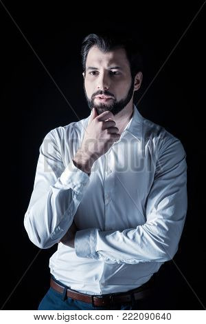 Serious problem. Handsome nice pensive man standing against black background and holding his chin while thinking about a serious problem