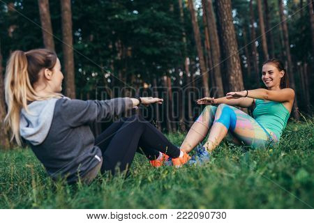 Two smiling sportswomen training outdoors doing full sit-ups sitting opposite each other on grass in forest.
