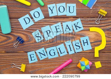Learning Foreign Languages concept: Do you speak English inscription on blue paper and bright colorful office supplies on a rustic wooden background, top view