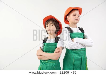 Waist up portrait of little boys being sure that their vocation is constructing. Their look is confident. Copy space in left side. Isolated on background