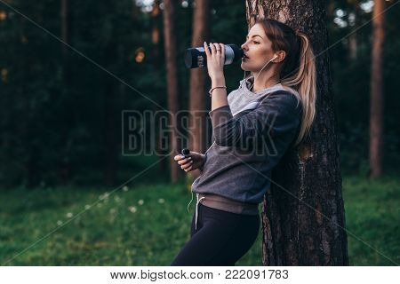 Female jogger recovering after intensive workout standing near the tree drinking water, wearing headphones in park.