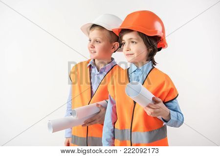 Great work. Future construction specialists with blueprints in hands looking at the new building with admiration. Isolated on background