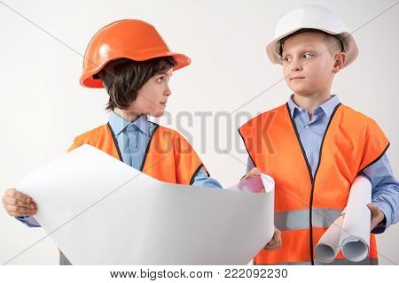 Little boys playing game as if they are builders. They are looking at each other with seriousness. Isolated on background