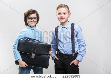 Waist up portrait of dreamful schoolchildren imagining themselves as big bosses. They are looking at camera with satisfaction. Isolated on background