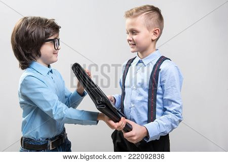 Waist up of smiling little youngsters playing game as if they are working in big company. Boy is giving briefcase to friend. Isolated on background