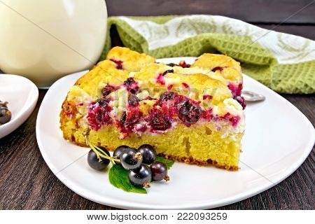 Piece of sweet pie with black currant berries and fork on a plate, napkin, milk in a glass jug on a background of a dark wooden board