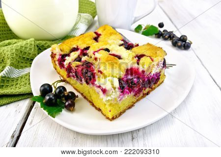 A piece of sweet pie with black currant berries and a fork on a plate, a napkin, milk in a glass jug against a light wooden board