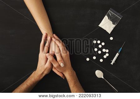 Drug addict hands asking for help on dark table with cooked heroine, pills, spoon and plastic bag. Concept for drug addiction and International Day against Drug Abuse, top view