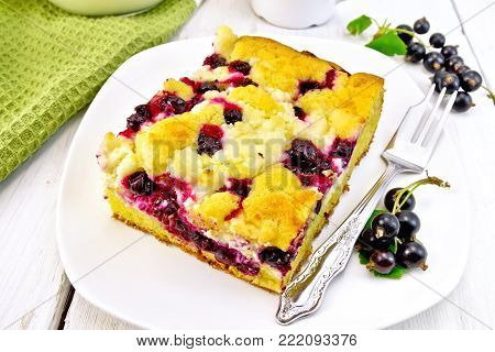 A piece of sweet pie with black currant berries and a fork on a white plate, a napkin on the background of a light wooden board
