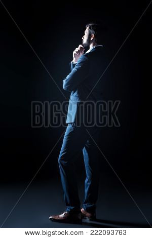 Thoughtful position. Nice handsome good looking businessman turning his back to you and being thoughtful while standing against black background