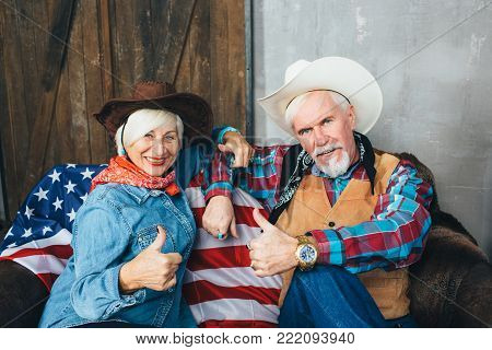 Elderly couple dressed in cowboy hats, showing thumbs up, smiling and looking at camera. Behind, on the couch lies the American flag, the celebration of America's Independence Day