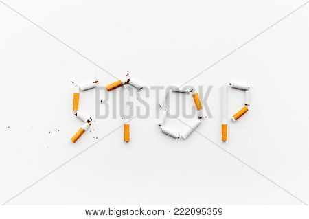 Stop smoking. Word stop lined cigarettes on white background top view.