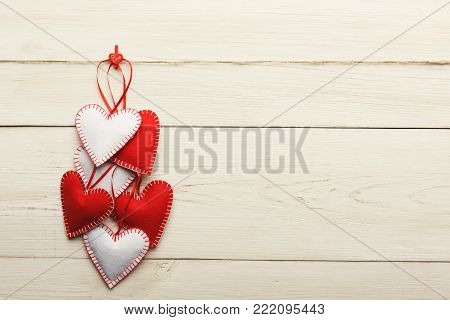 Valentine background with diy handmade sewed pillow hearts on red clothespins at rustic white wood planks. Happy lovers day card mockup, copy space, top view