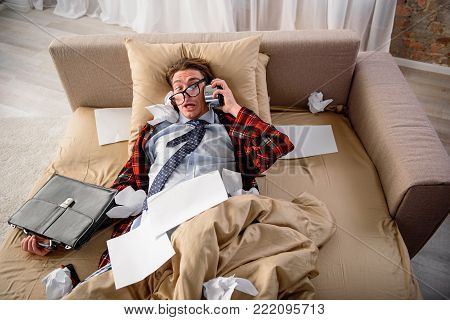 Stop ringing. Scared guy lying in bed with frightened look. He is holding alarm clock while listening to it in bedroom