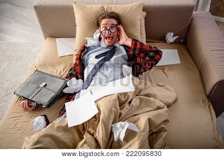 Scared guy lying in bed and screaming. He is looking at camera with frightened look and holding a briefcase. Top view