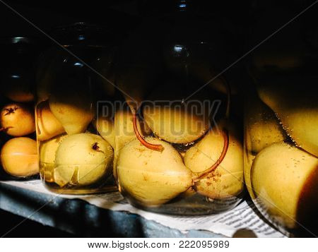 Delicious canned yellow pears in a dark cellar. Compote. Home winter snack in glass jar. Photo of glass with pear isolated  on background. Canned pears in the bank. Close up.
