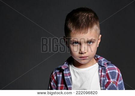 Sad little boy being bullied at school on dark background