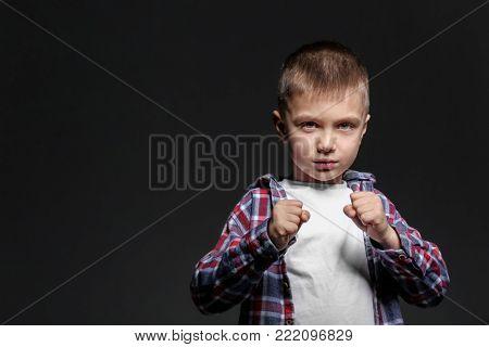 Portrait of bully boy on dark background