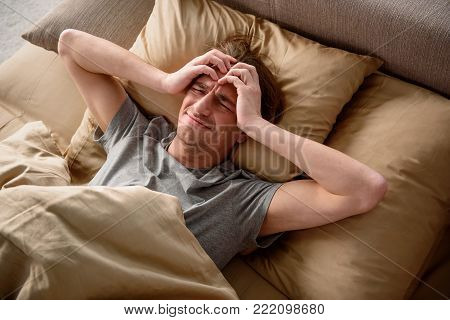 Exhausted adult male suffering from a migraine in bedroom. He is lying in bed with a grimace on his face