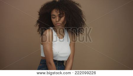 mixed race black woman portrait with big afro hair, curly hair in beige background with wind blowing her hair