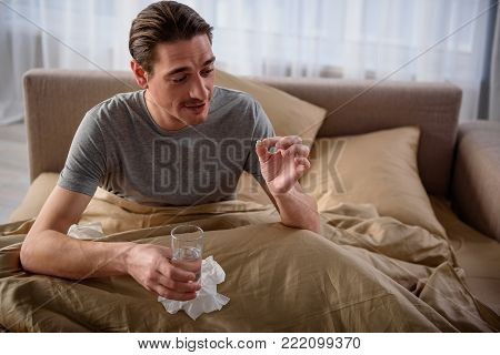 Waist up portrait of calm guy sitting on bed and having water glass in the hand. He is treating himself with pill