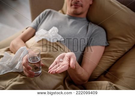 Terribly ill man is lying in bed and taking medicine. Focus on male hands holding a glass of water and pill. Top view close up