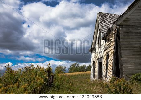 Derelict house in New Brunswick, Canada. Side view with overgrown meadow and summer sky.