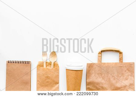 Disposable tableware. Paper cup, spoon, fork near brown paper bag and notebook top view copy space mock up.