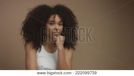mixed race black woman portrait with big afro hair, curly hair in beige background. Thinking about something with a hand on chin