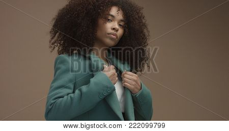 mixed race black woman portrait with big afro hair, curly hair in beige background wearing green coat. Closeup