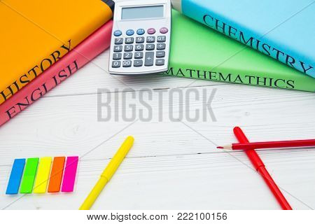 Education concept. Doing homework. Student's books, a calculator and stationary on a white wooden table