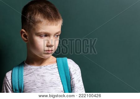Sad little boy being bullied at school on color background