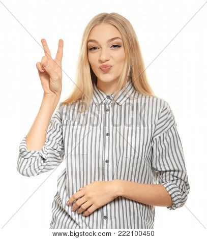 Young funny woman showing victory gesture on white background