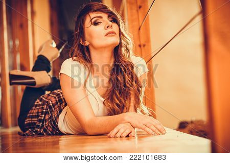 Alluring seductive gorgeous woman. Attractive young girl with long hair wearing white shirt and jeans trousers laying on floor at home. Instagram filter.