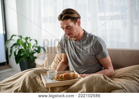 Waist up portrait of serious man sitting on bed and holding the tray. He is looking at croissant on salver with pensiveness