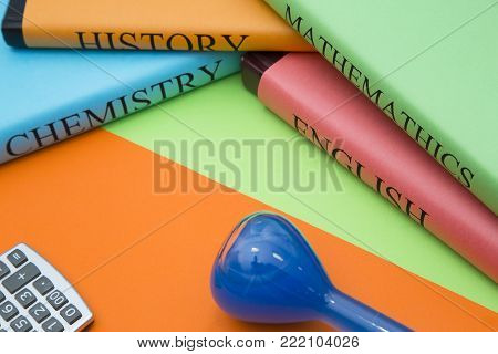 Education concept: A stack of student's books, calculator and a beaker with a blue liquid on a bright orange and green background with copy space