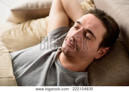 Tranquil man slumbering on bed. His eyes are closed with serenity. Relaxation concept